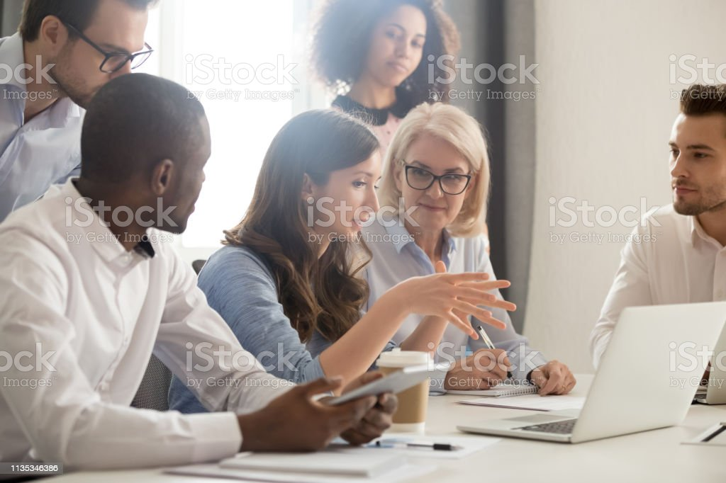 Female mentor teaching employees group analyzing online project explaining strategy Young female mentor leader coach teaching employees group analyzing online project explaining business strategy speaking training diverse corporate team with laptop using computer at office meeting Adult Stock Photo