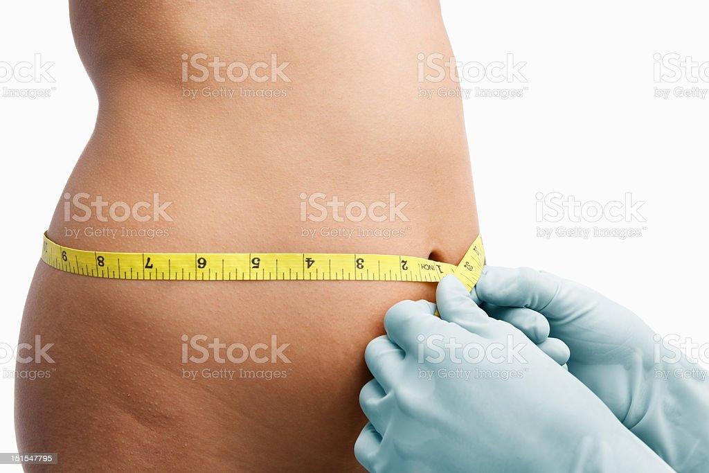 Female mid section being measure before liposuction royalty-free stock photo