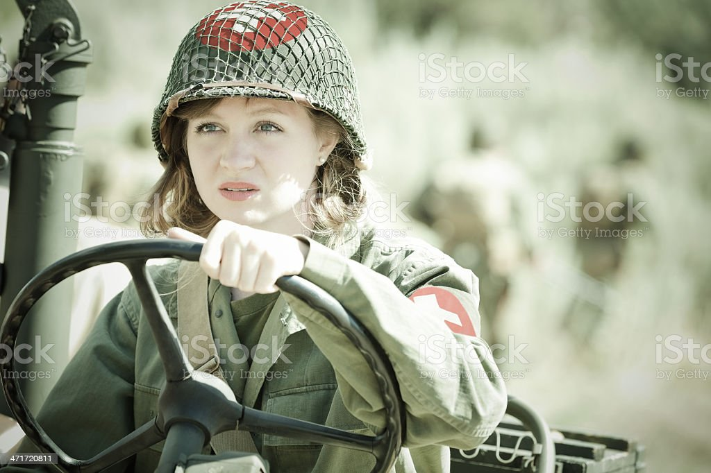 Female military medic driving vehicle in field stock photo