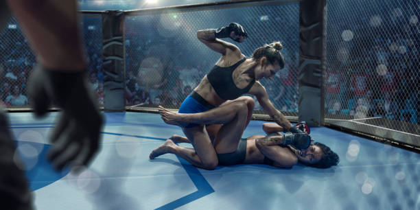 female mixed martial arts fighters grappling in octagon during competition - combat sport stock pictures, royalty-free photos & images