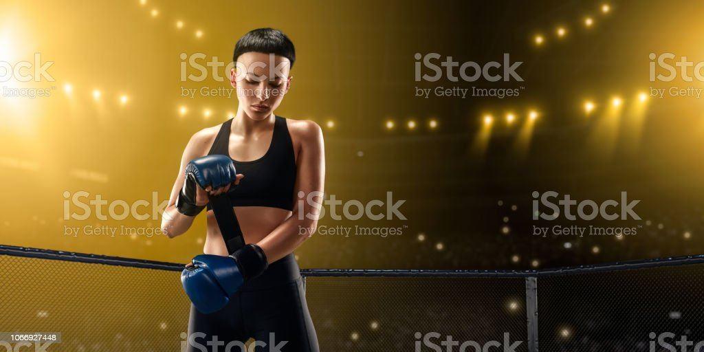 Female MMA fighter in professional boxing ring stock photo