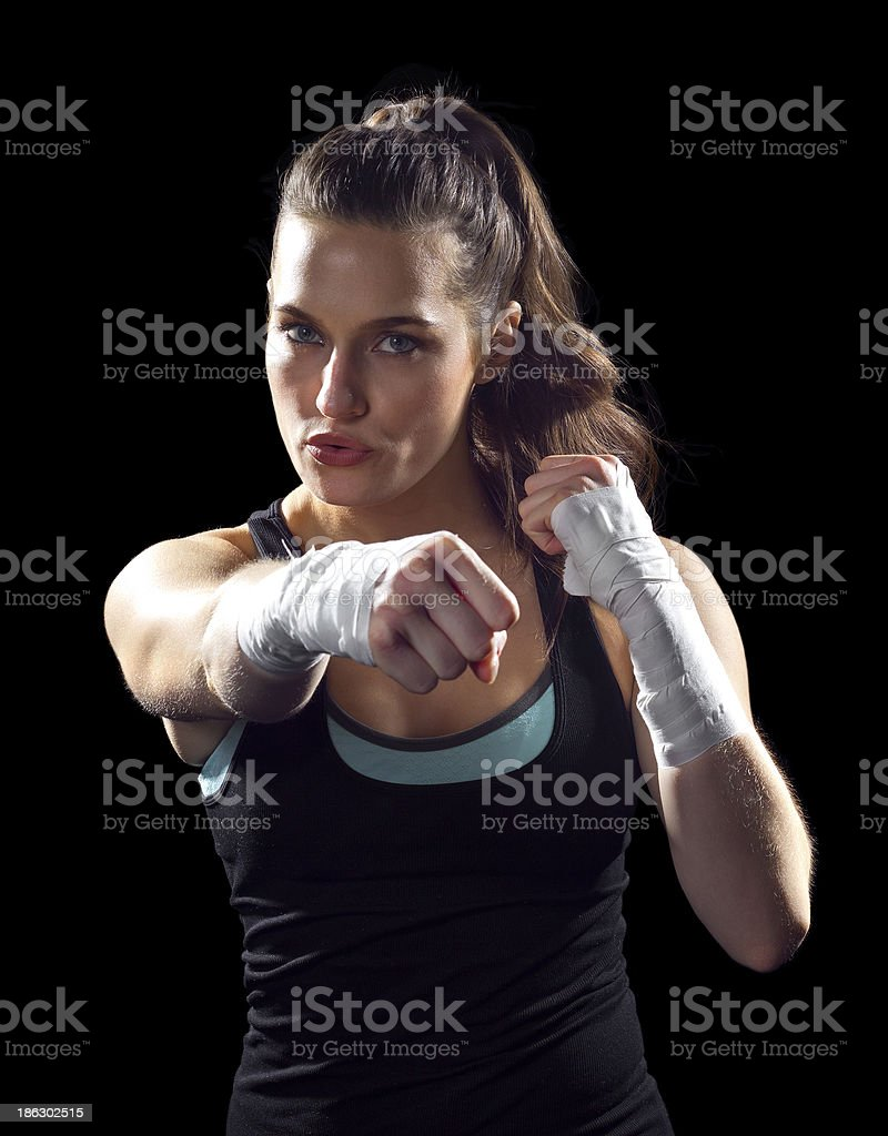 Female MMA fighter punching on black background royalty-free stock photo