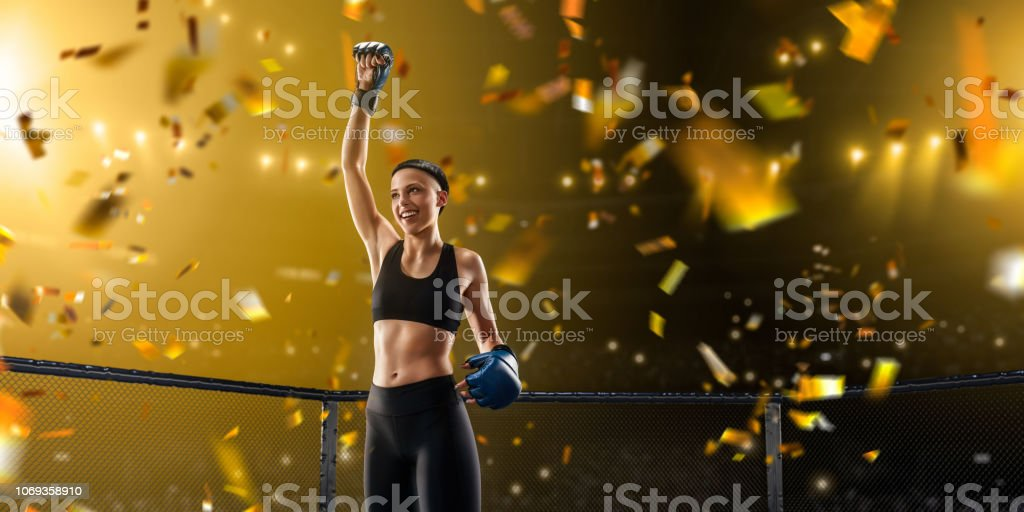 Female MMA fighter rejoices in victory in professional boxing ring stock photo