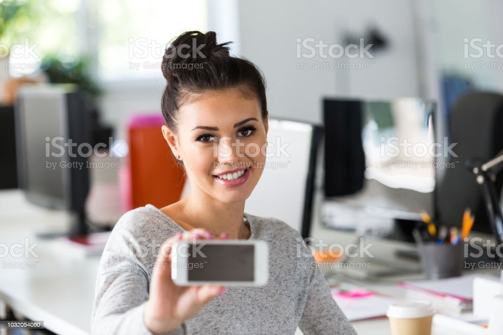 Female mobile app developer showing a smart phone Portrait of beautiful young woman showing a mobile phone to the camera while sitting at the desk. Mobile application developer at office. 20-24 Years Stock Photo