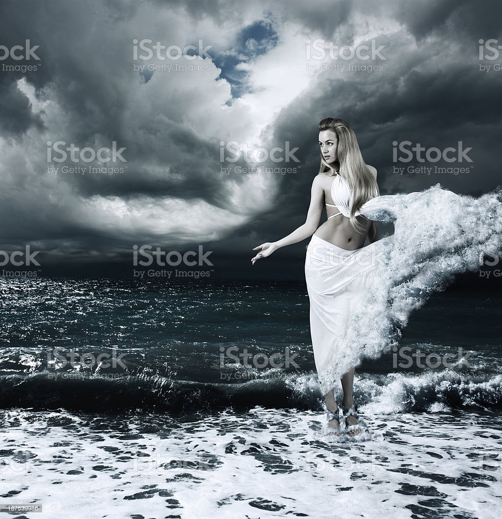 Female model dressed as a goddess by a stormy sea stock photo