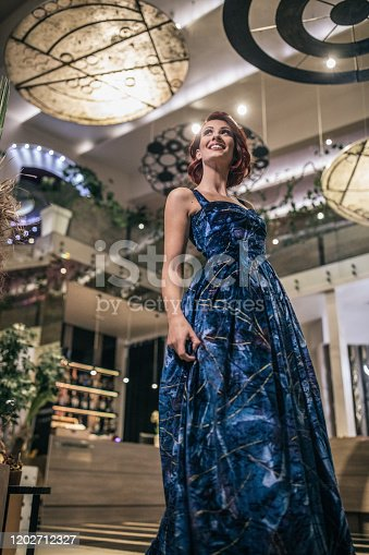 Beautiful young female fashion model in elegant blue long dress