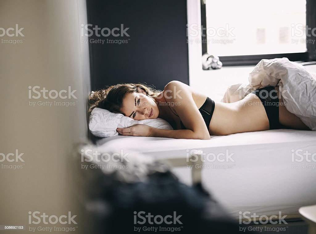 Female model in lingerie lying on her bed stock photo