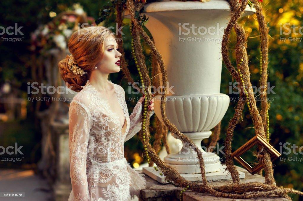 Female model posing beside stone balustrade and large flower vas stock photo