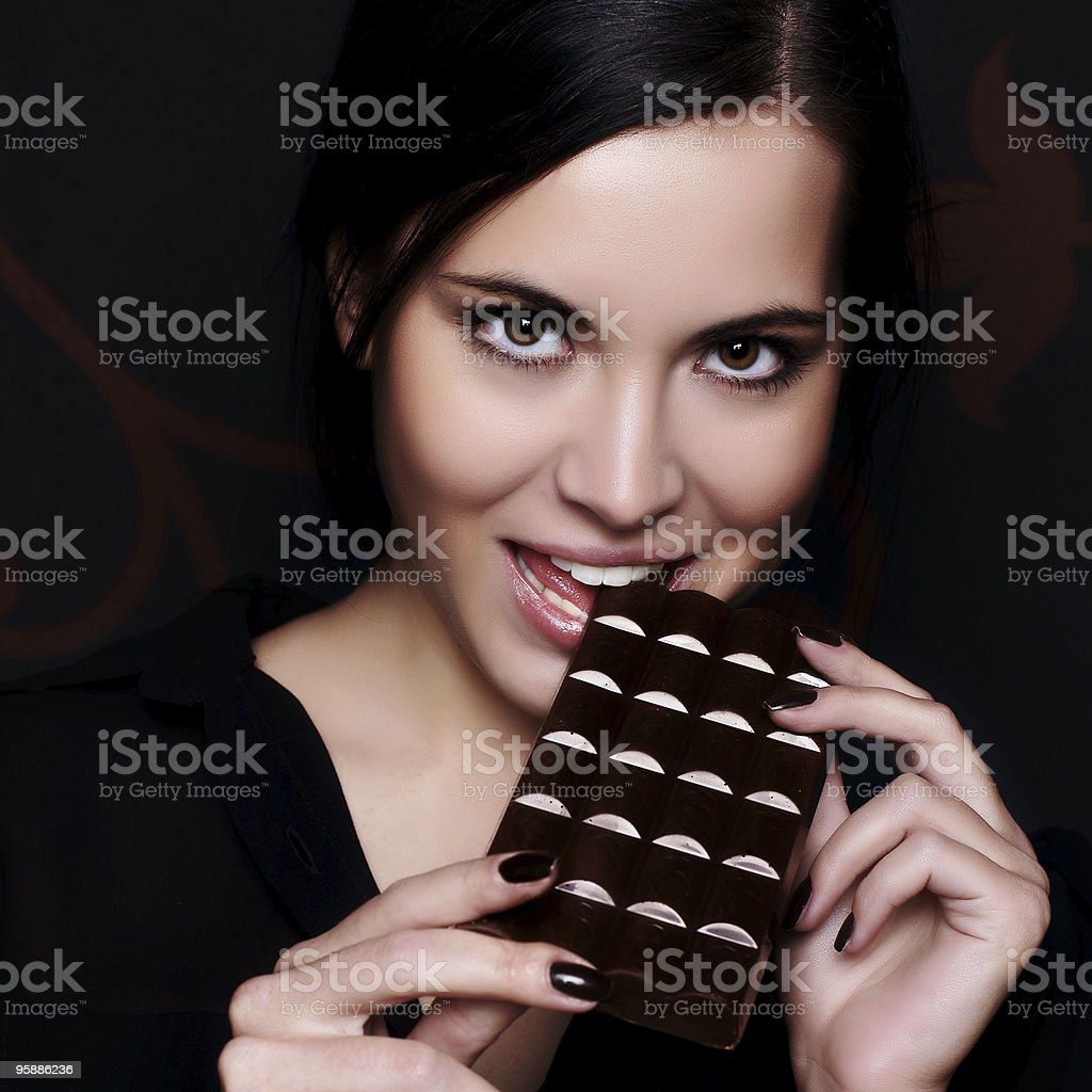 Female model posing with a large bar of chocolate stock photo