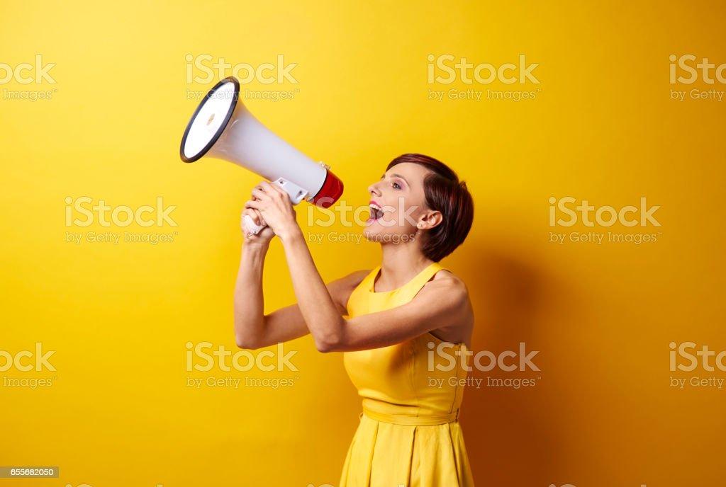 Female model using bullhorn in photo session stock photo