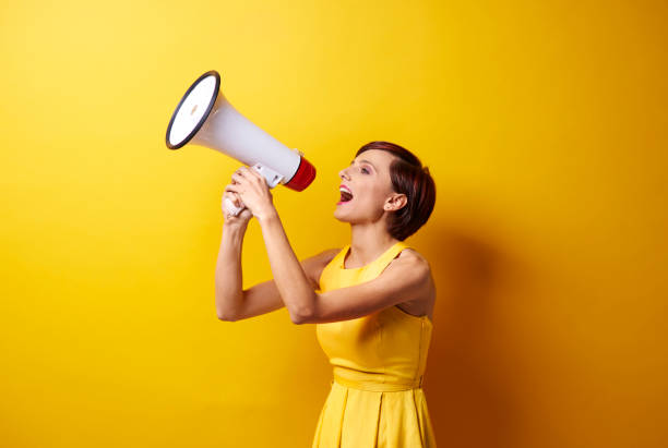 Female model using bullhorn in photo session stock photo