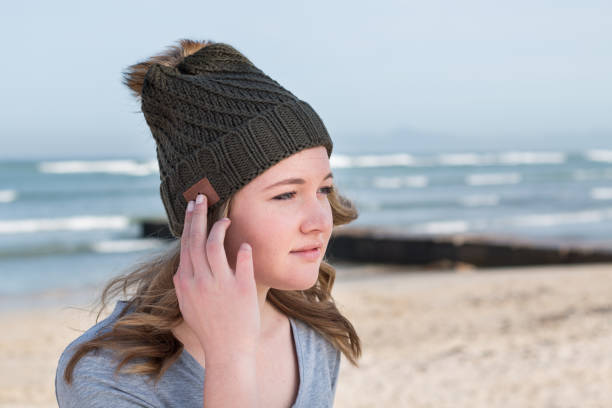 Female model wearing green knitted beanie with Bluetooth speakers stock photo