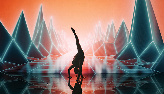 Young woman dancing. Wearing modern outfit and futuristic make up. Purple, futuristic mountains and rocks video in background. Digitally generated