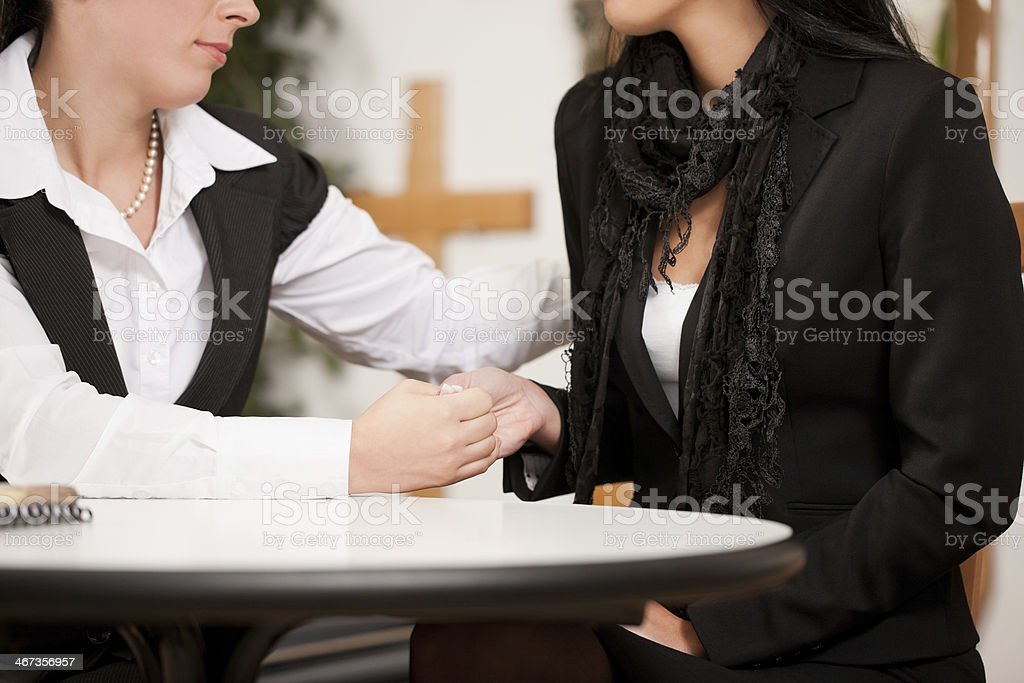 Female mortician comforting and advising a woman in black stock photo