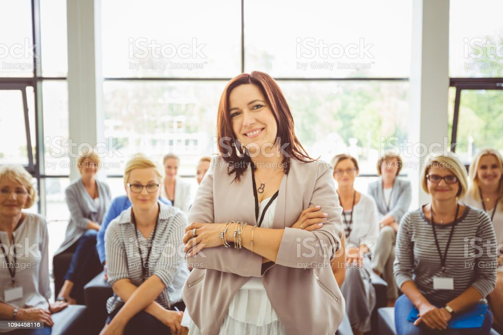 Female motivational speaker with audience at back Portrait of mature female speaker with audience sitting in background Adult Stock Photo