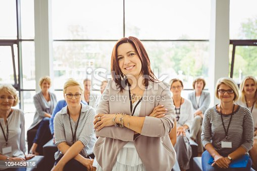 854811490istockphoto Female motivational speaker with audience at back 1094458116