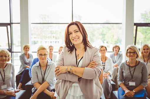 Female Motivational Speaker With Audience At Back Stock Photo - Download Image Now