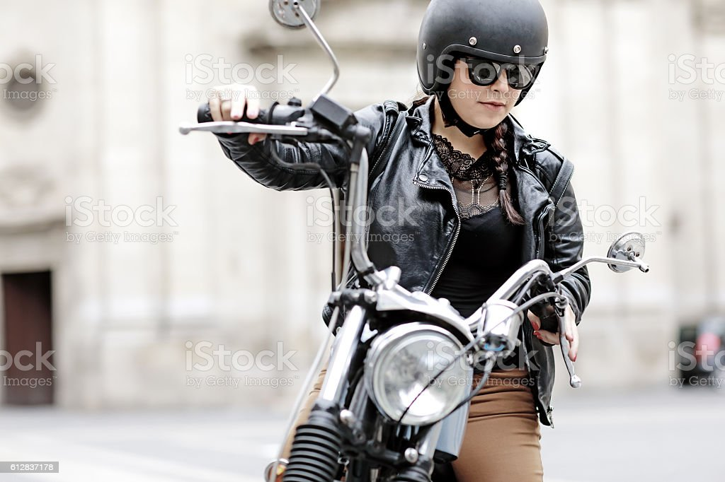 Female motorcyclist preparing for a ride on a vintage motorbike - foto de acervo