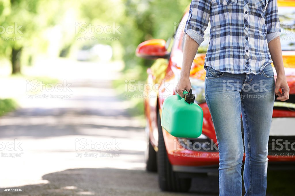 Female Motorist Carrying Fuel Can Next To Broken Down Car stock photo