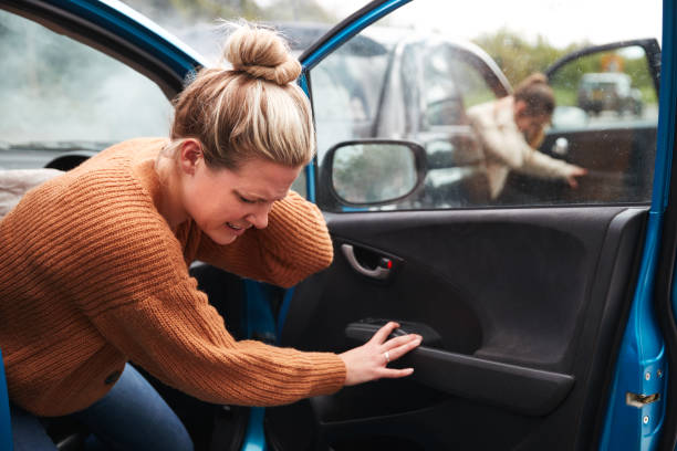 Female Motorist In Crash For Crash Insurance Fraud Getting Out Of Car stock photo
