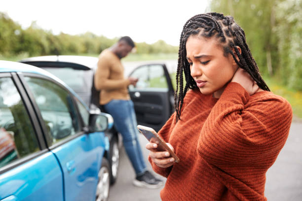 Female Motorist Involved In Car Accident Calling Insurance Company Or Recovery Service Female Motorist Involved In Car Accident Calling Insurance Company Or Recovery Service physical injury stock pictures, royalty-free photos & images