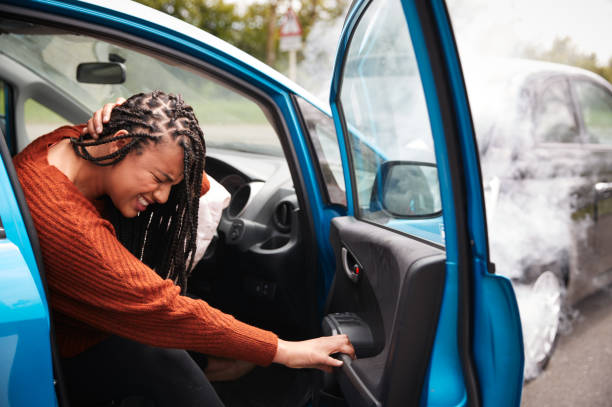 Female Motorist With Whiplash Injury In Car Crash Getting Out Of Vehicle stock photo
