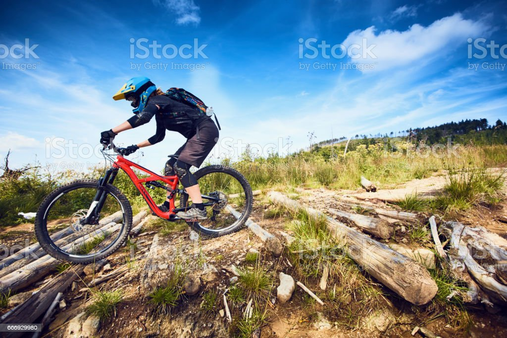 Female Mountain Bike cyclist riding track at sunny day in European mountains stock photo