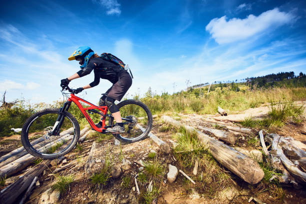 female mountain bike cyclist riding track at sunny day in european mountains - mountain biking stock photos and pictures
