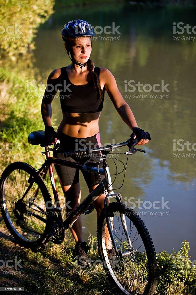 Female mountain biker by pond royalty-free stock photo