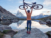 istock Female mountain biker holds bicycle overhead from Riffelsee Lake below the Matterhorn 1286891004