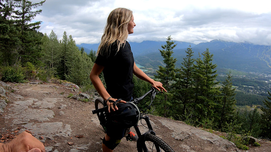 Female mountain biker removes helmet and looks out