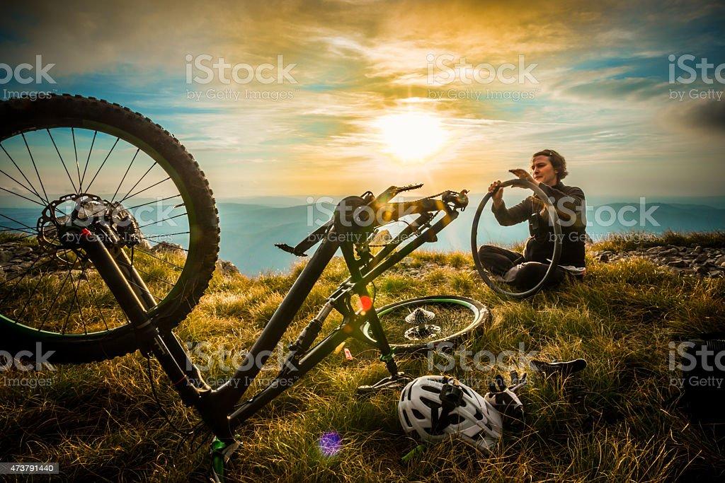 Female Mountain Biker Repairing her Bike stock photo