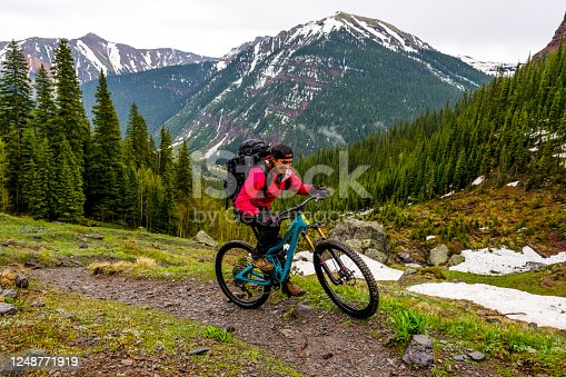 She smiles as she rides past snow patches, mountain range behind