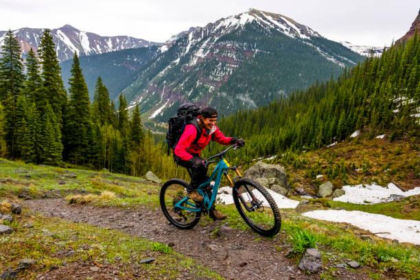 Female mountain biker rides along mountain ridge stock photo