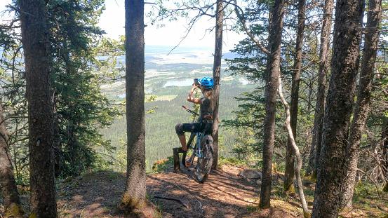 Female mountain biker takes photos on phone at viewpoint