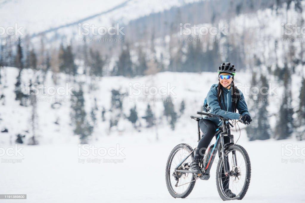 Weibliche Mountainbiker mit Fahrrad stehen im Freien in der Winternatur. - Lizenzfrei Abenteuer Stock-Foto