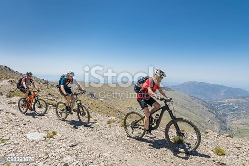 A senior adult female mountainbike guide is leading male mountainbikers on their way uphill high up in the Andalucian Sierra Nevada which is a mountain range in the province of Granada and, a little further, Málaga and Almería in Spain. It contains the highest point of continental Spain and the third highest in Europe after the Caucasus Mountains and the Alps, Mulhacén at 3,479 metres (11,414 ft) above sea level. It is a popular tourist destination. Parts of the range have been included in the Sierra Nevada National Park. The range has also been declared a biosphere reserve. Canon EOS 5D Mark IV, 1/320, f/11, 24 mm.