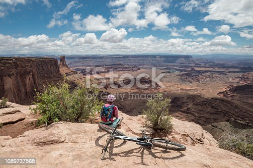 A female mountainbiker is taking a break overlooking Canynonlands National Park from the rim of Dead Horse Point State Park. Dead Horse Point State Park is a state park of Utah in the United States, featuring a dramatic overlook of the Colorado River and Canyonlands National Park. The park covers 5,362 acres (2,170 ha) of high desert at an altitude of 5,900 feet (1,800 m). Canon EOS 5D Mark IV, 1/160, f/16, 24 mm.