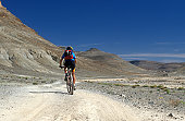istock Female Mountainbiker in the mountain desert of Morocco 136147417