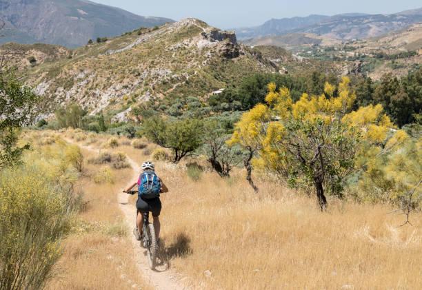 Weibliche Mountainbiker auf schmalen Singletrail in der andalusischen Sierra Nevada. – Foto