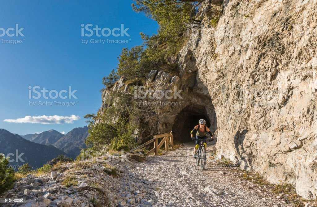Female mountainbiker on rocky downhill out of tunnel, Italy stock photo