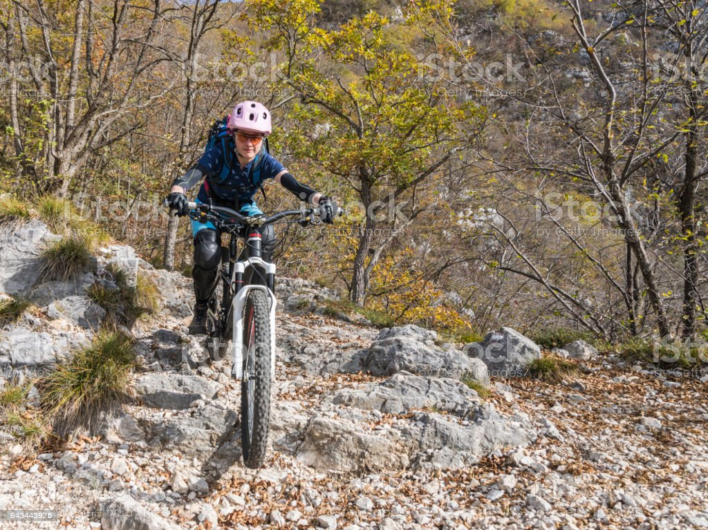 Female mountainbiker on rocky downhill turn at Lake Garda, Italy. stock photo