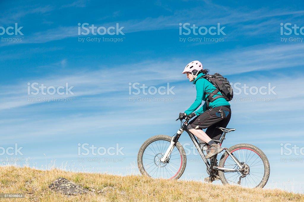 Female mountainbiker uphill, Switzerland stock photo