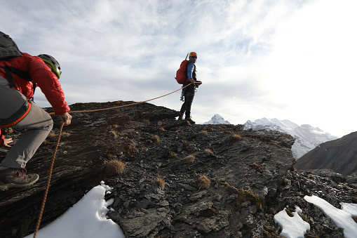 istock Female mountaineer climbs to summit belay 937198778