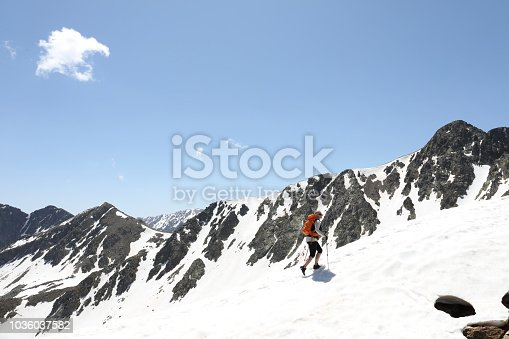 Female mountaineer hikes up through mountains on snow trail in Andorra