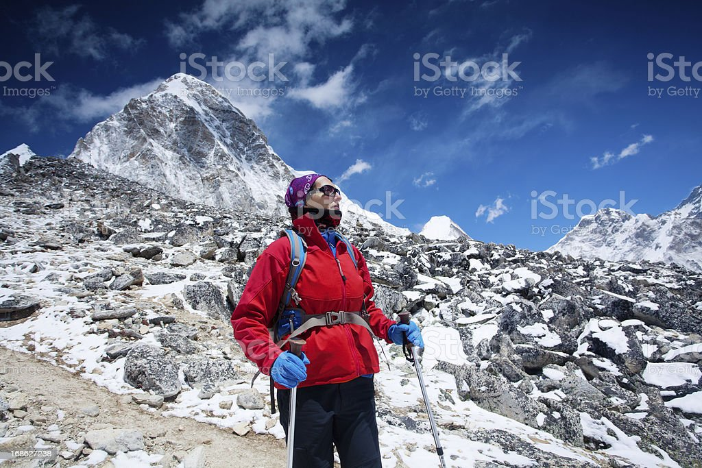 Female mountaineer standing alone on the mountain and looking aw royalty-free stock photo