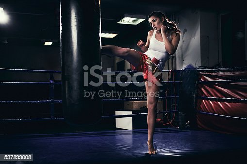 873932790 istock photo Female muay thai fighter training with a punching bag 537833008