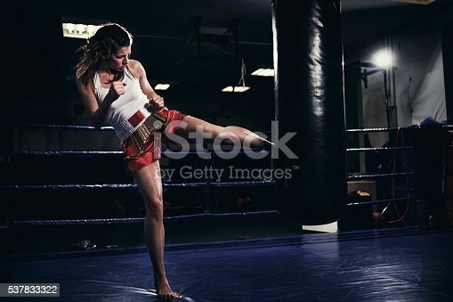 873932790 istock photo Female muay thai fighter training with a punching bag 537833322