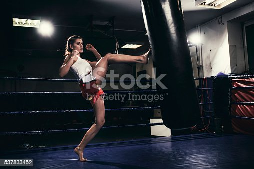 873932790 istock photo Female muay thai fighter training with a punching bag 537833452