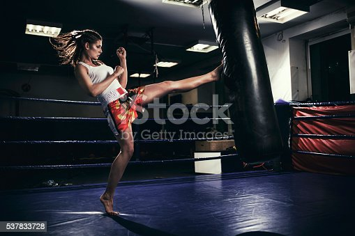 873932790 istock photo Female muay thai fighter training with a punching bag 537833728